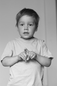 child signing using BSL sign language